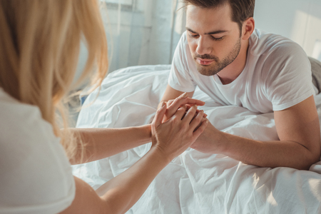handsome man touching hands of girlfriend while laying in bed Stock Photo