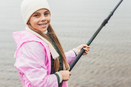 smiling little girl in raincoat fishing on cold autumn day