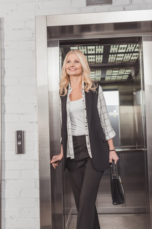 mature stylish woman going out of elevator