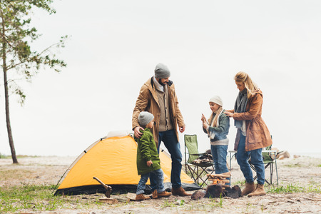 beautiful family having camping trip on cold cloudy day