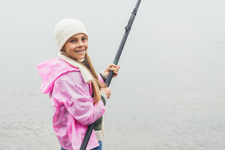 happy little girl in raincoat fishing on cold autumn day