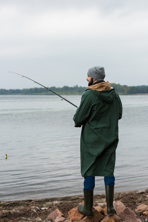 bearded man in raincoat and warm clothing fishing on lake