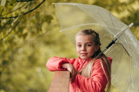 cute little child holding umbrella and looking at camera in autumn park