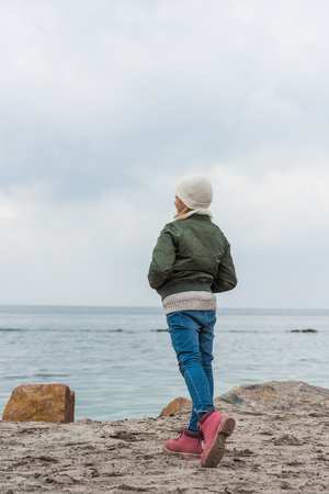 little girl standing on coast and looking at sea ol cold autumn day