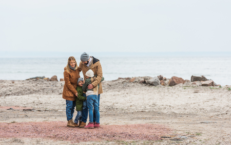 beautiful family emracing on seashore on cold autumn day