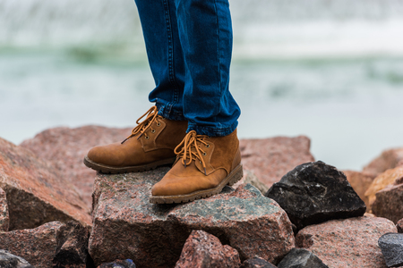 cropped shot of man in stylish shoes standing on rocks