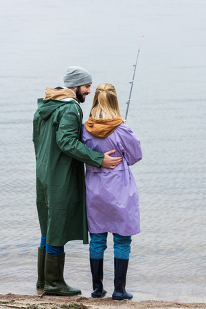 young couple in raincoats fishing together Stock Photo