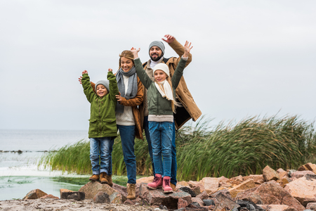 happy young family with raised hands on seashore