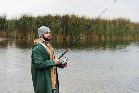 happy man in raincoat and warm clothing fishing on lake