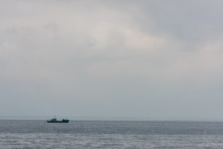 lonely ship floating in sea on cloudy day 写真素材