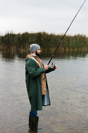 lonely man in raincoat and warm clothing fishing on lake