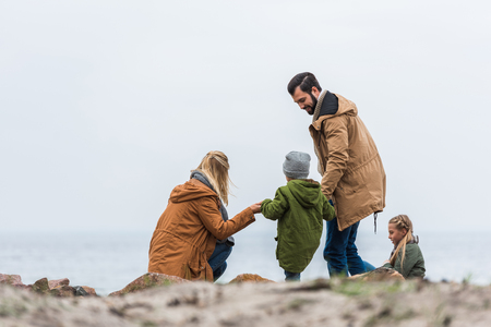 happy family spending time on seashore on cold autumn day Stok Fotoğraf