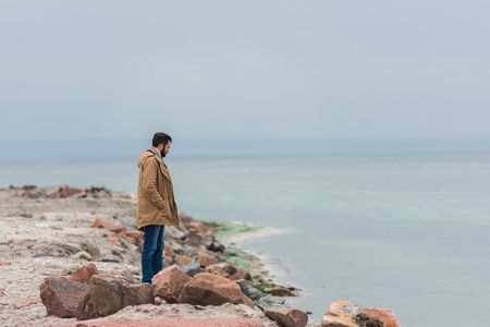 lonely sad man standing on rocky seashore Stock Photo