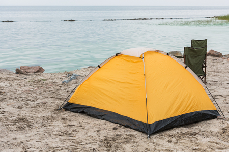 camping tent with two chairs standing on seahore on cloudy day Imagens - 102649875