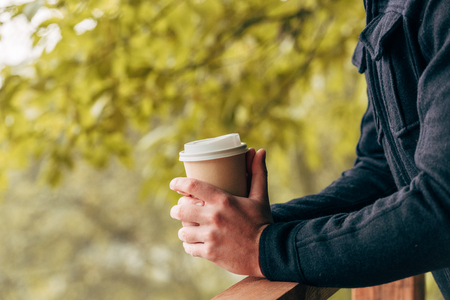 cropped shot of young man holding disposable coffee cup in autumn park