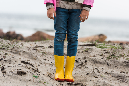 cropped shot of little child in raincoat and rubber boots on sandy beach alone Reklamní fotografie