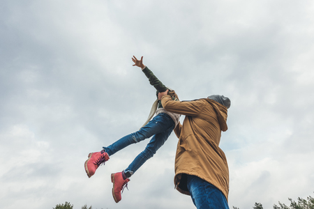 father throwing up his daughter against cloudy autumn sky