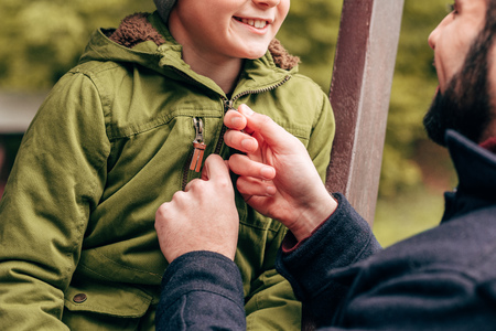 cropped shot of father fastening jacket of cute smiling little son in park