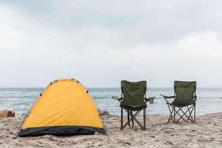 camping tent with two chairs standing on seahore Фото со стока