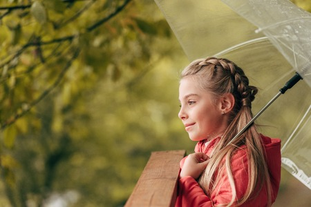 side view of smiling little child holding umbrella and looking away in autumn park