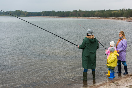 family in raincoats and rubber boots fishing together in lake