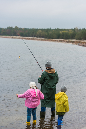 father and two little kids fishing together at mountain lake