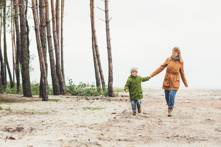 mother and son walking together on nature by sandy coast Stok Fotoğraf