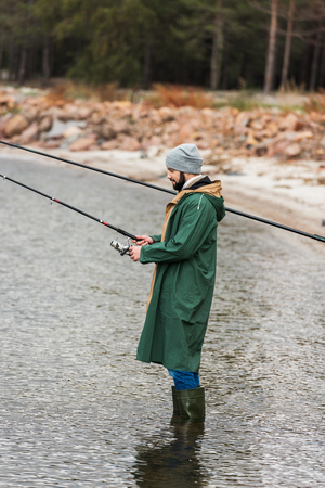 side view of man in raincoat and warm clothing fishing on lake
