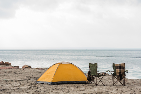 lonely camping tent with two chairs standing on seahore