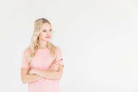 beautiful smiling young woman standing with crossed arms and looking away isolated on white Banque d'images - 102662581