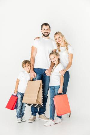 glückliche Familie, die Einkaufstaschen hält und an Kamera lokalisiert auf Weiß lächelt