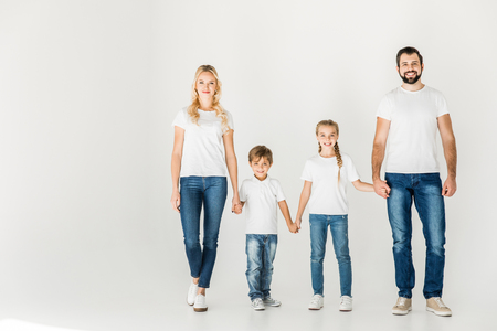 happy young family in white t-shirts holding hands and walking together isolated on white
