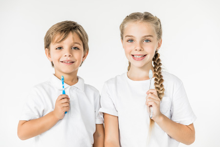 kids holding toothbrushes and smiling at camera isolated on white