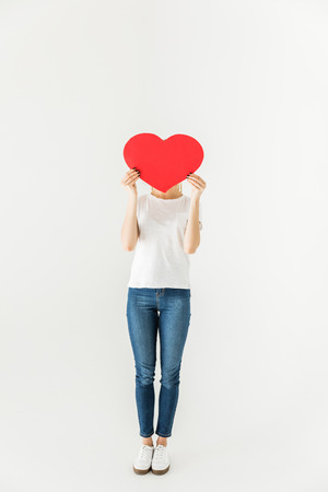 young woman hiding face behind red heart symbol isolated on white 스톡 콘텐츠