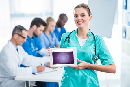 attractive young nurse holding tablet with colleagues sitting at table on background Editorial
