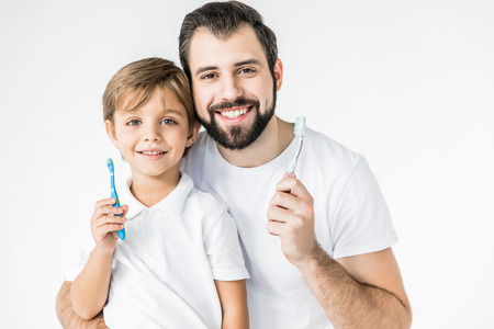 happy father and son holding toothbrushes and smiling at camera isolated on white