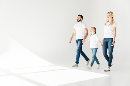 full length view of young family holding hands and walking  on white