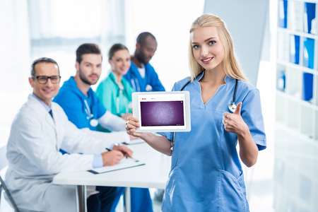 smiling young nurse holding tablet and showing thumb up with colleagues sitting at table on background Editorial