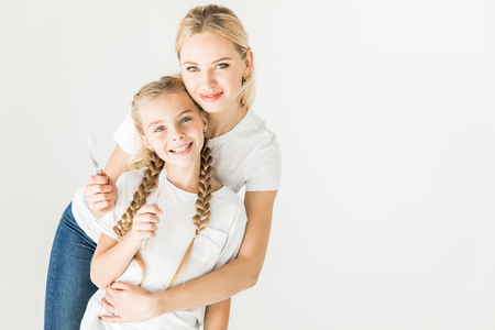 happy mother and daughter holding toothbrushes and smiling at camera isolated on white