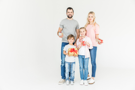happy family holding gift boxes and smiling at camera isolated on white