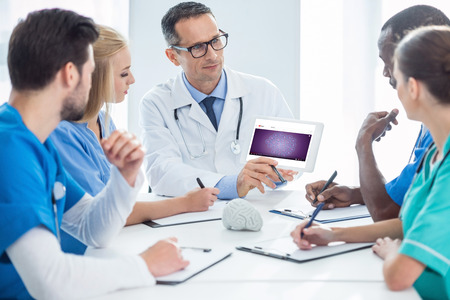 team of doctors having conversation and looking at digital tablet Editorial