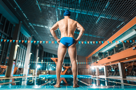 back view of muscular sportsman in swimming cap and goggles standing at swimming pool