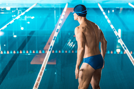 back view of muscular swimmer in swimming cap and goggles standing at swimming pool Reklamní fotografie