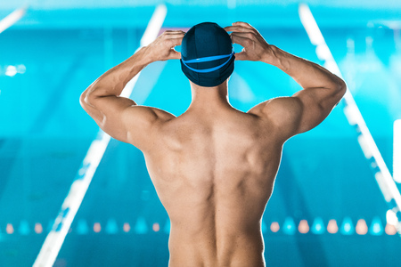back view of muscular swimmer in swimming cap and goggles standing at swimming pool Standard-Bild - 102650161