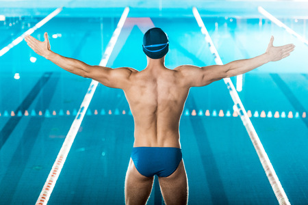 back view of muscular swimmer in swimming cap and goggles standing at swimming pool Imagens