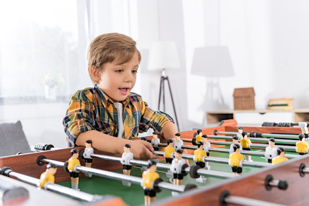 happy little boy playing table football