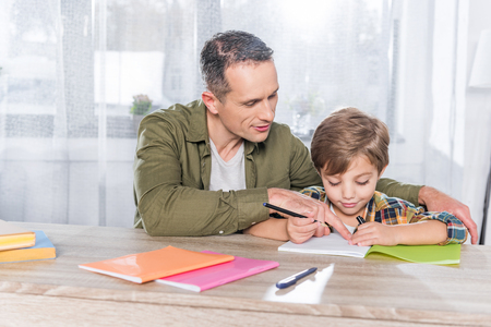 father and adorable son doing homework together at home Stock fotó
