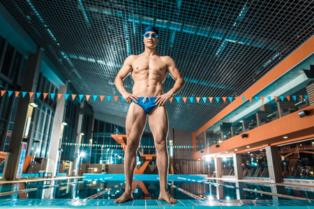handsome muscular swimmer in swimming cap and goggles posing at swimming pool Imagens