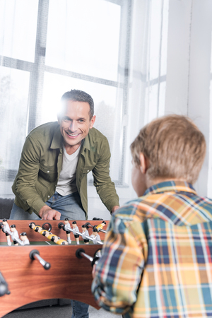 happy handsome father and son playing kicker at home Stock Photo