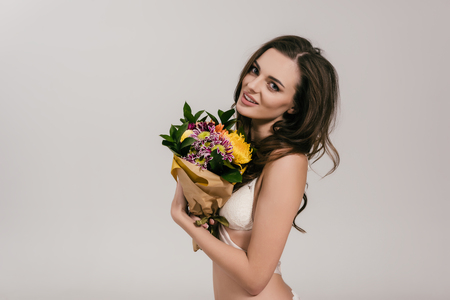 beautiful girl in lingerie holding flowers and smiling at camera isolated on grey